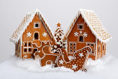 Le case di pan di zenzero commestibili fatte a mano, le renne e il carretto, l'albero di Capodanno con decorazioni di neve