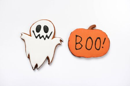 The hand-made eatable gingerbread Halloween ghost and pumpkin with boo inscription on white background
