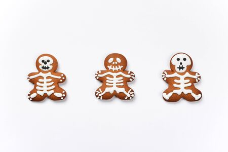 The hand-made eatable gingerbread Halloween sceletons on white background