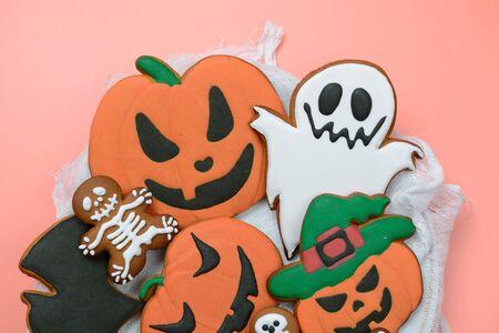 La citrouille d'Halloween en pain d'épice comestible faite à la main, les fantômes, la chauve-souris et les squelettes sur fond rose