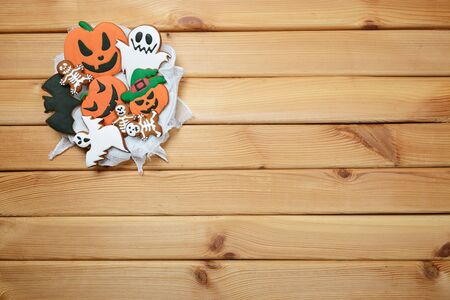 The hand-made eatable gingerbread Halloween pumpkin, ghosts, bat and sceletons on wooden background Stock Photo