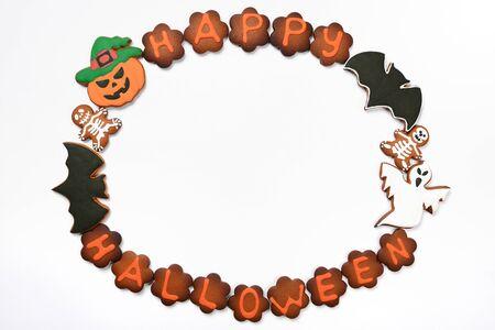 L'inscription d'Halloween en pain d'épice comestible fait à la main, la citrouille, les fantômes et les squelettes sur fond blanc