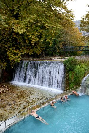 LOUTRA, ARIDEA, GREECE-OCTOBER 13: The tourists swimming in water from hot springs in Loutra, Aridea on October 13, 2013 in Loutra, Aridea, Greece. Up to 12 mln tourists is expected to visit Greece in year 2013 新聞圖片