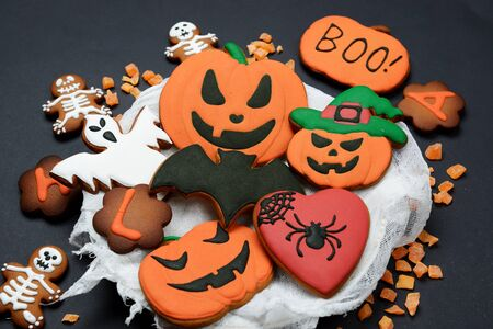 The hand-made eatable gingerbread Halloween pumpkin, ghosts, bat and sceletons on black background Banque d'images