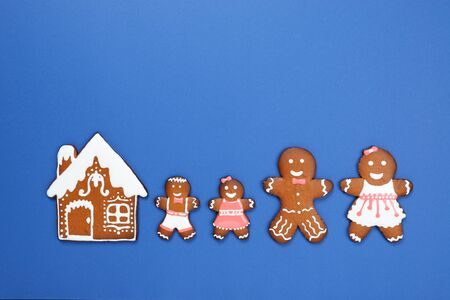 The hand-made eatable gingerbread house, little men on blue background Stock Photo