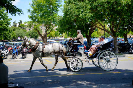 KERKYRA, GREEES - MAY 17: The tourists are in horse-drawn carriage on street on May 17, 2016 in Kerkyra, Greece. Up to 16 mln tourists is expected to visit Greece in year 2016.