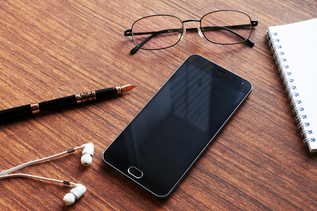 earpiece: View of business have a phone, notebook, Goggles, headphones, pen and mobile phone with on wooden red background