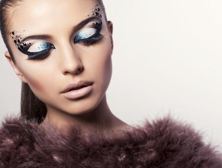 smokey: fashion studio photo of beautiful girl with extravagant eyes makeup and fur