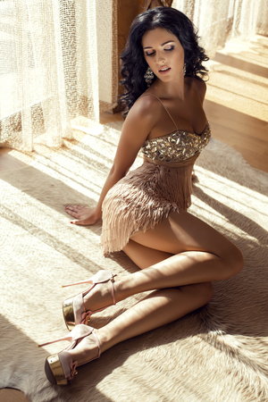 fashion photo of beautiful glamour woman with black hair in luxurious dress lying on carpet at bedroom in sunlight rays photo