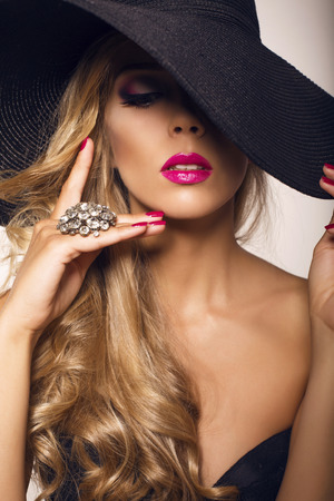 sexy glamour: studio fashion photo of sexy glamour model with blond curly hair in elegant black hat with ring