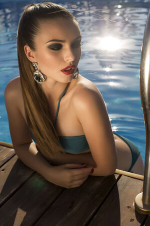 swimsuite: fashion photo of beautiful glamour brunette in bikini with bijou posing in swimming pool