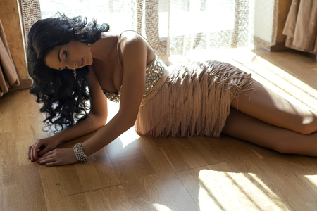 fashion photo of beautiful glamour woman with black hair lying on wood floor at bedroom in sunlight rays photo