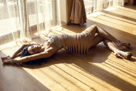 fashion photo of beautiful glamour woman with black hair in luxurious beige dress lying on wood floor at bedroom in sunlight rays photo