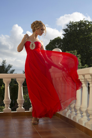 ladylike: fashion photo of beautiful glamour model with elegant hairstyle in luxurious silk red dress posing on balcony