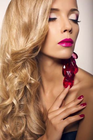 sensual lips: studio fashion photo of beautiful model with blond curly hair with bright makeup and bijou