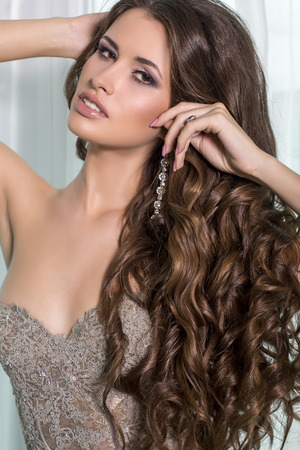 fashion portrait of beautiful brunette with luxurious hair