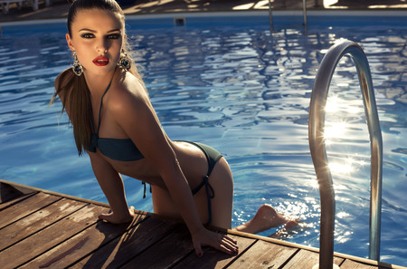 swimsuite: fashion photo of beautiful glamour brunette in bikini with bijou posing in swimming pool