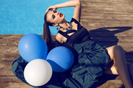 chic woman: fashion portrait of beautiful glamour young woman in elegant dress and bijou holding white and blue balloons,lying beside a swimming pool