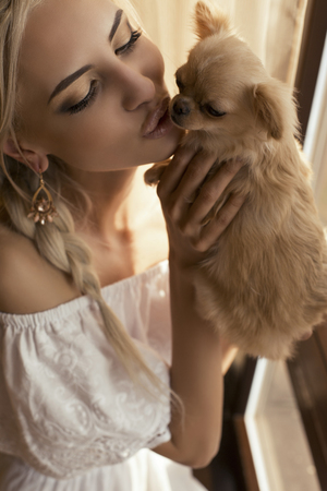 ladylike: tender photo of beautiful glamour girl with blond hair kissing a small adorable dog Stock Photo