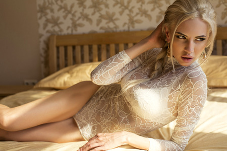 sexy glamour: fashion photo of sexy glamour woman with blond hair in white lace lingerie lying on bed at bedroom