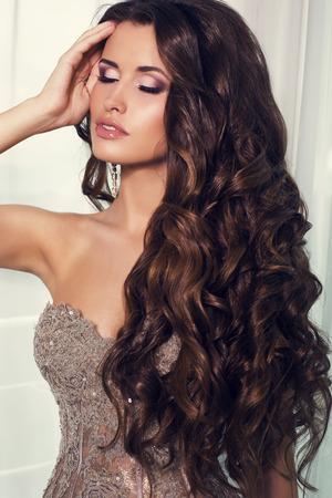 Мода фото сексуальная красивая женщина с длинными темными вьющимися волосами в роскошном платье позирует у окна