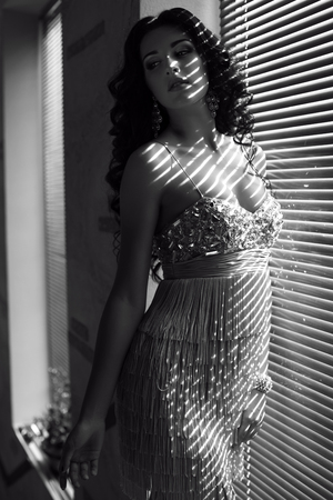 black and white fashion photo of beautiful glamour woman with black hair posing at bedroom in sunlight rays photo