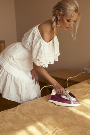 iron curtain: photo of sexy beautiful woman with blond hair in elegant white dress ironing sheet Stock Photo