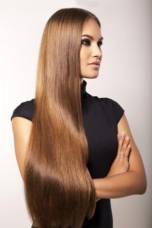 fashion studio photo of beautiful woman with long straight dark hair in elegant black dress