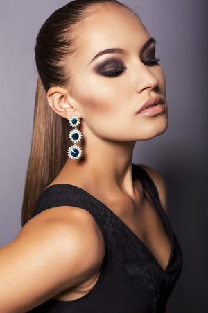 smokey: fashion portrait of sexy glamour woman with dark straight hair  in black dress and bijou posing at studio Stock Photo