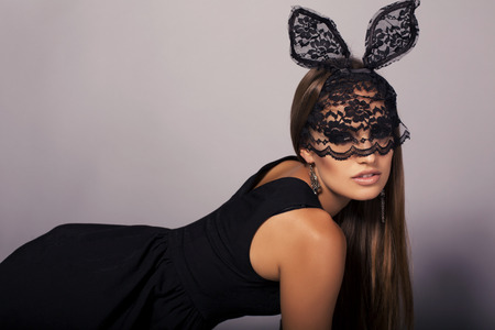 sexy glamour: fashion studio photo of sexy glamour model with long straight hair in elegant black dress with lace bunnys mask