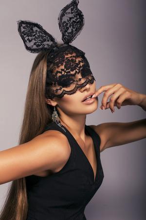레이스 토끼 마스크에 우아한 검은 드레스에 긴 직선 머리 섹시 한 여자의 패션 스튜디오 초상화