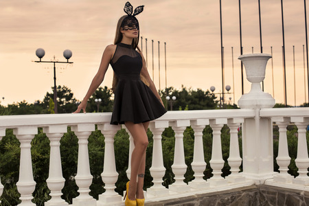 fashion photo of sexy glamour woman with dark hair in luxurious black dress and bunny mask posing on sky background