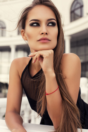 fashion photo of beautiful glamour model with long straight hair in elegant black dress posing at balcony photo