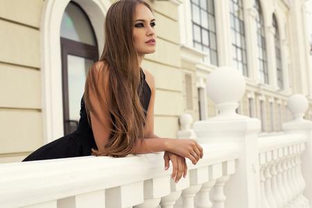 fashion photo of sexy glamour model with long dark hair in elegant black dress posing on balcony