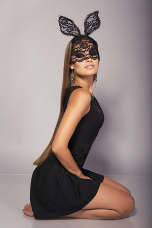 fashion studio photo of sexy glamour model with long dark straight hair in elegant black dress and lace bunny mask