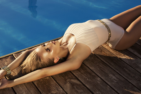 fashion photo of sexy beautiful model with blond hair in swimsuite relaxing beside a swimming pool