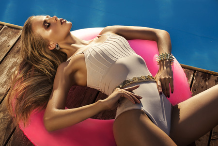 fashion photo of sexy glamour model with long blond hair in beige swimsuit and accessories lying on inflatable circle beside a swimming pool