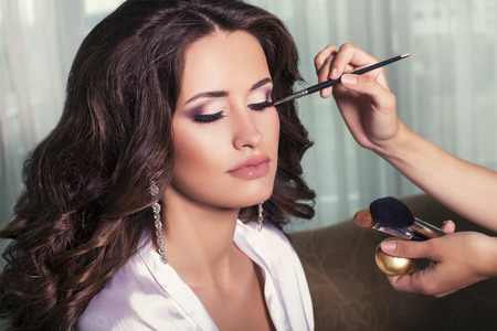 sexy bride: portrait of beautiful glamour woman with dark curly hair,visagiste finishing make up to bride at wedding morning Stock Photo