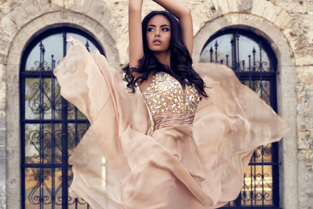 ladylike:   fashion photo of beautiful glamour model with long dark hair  in luxurious silk beige dress posing on castle background
