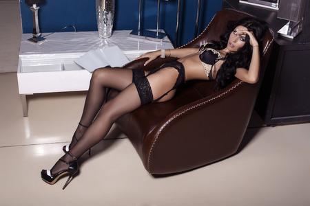 pantimedias: Foto de la moda de mujer sexy con el pelo negro en la ropa interior y pantimedias que presenta en el dormitorio Foto de archivo
