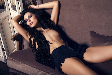 sexy glamour: fashion photo of sexy glamour woman with long black hair lying on divan at bedroom