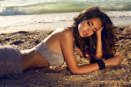 luxurious: fashion photo of sensual beautiful woman with dark hair in luxurious dress posing on summer beach in sunlight rays