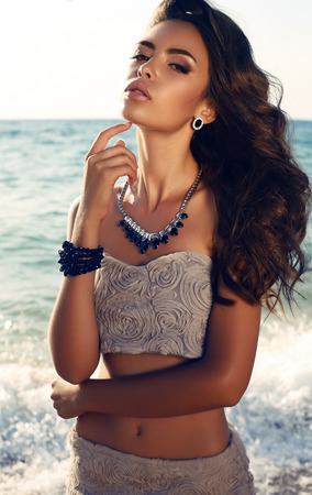 fashion photo of sensual beautiful woman with dark hair in elegant dress posing on summer beach in sunlight rays