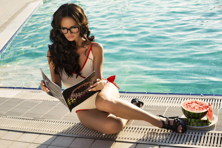 fashion photo of sexy glamour model with dark hair in glasses reading magazine relaxing beside a swimming pool
