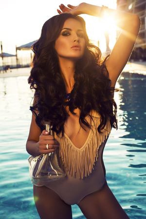 fashion photo of sexy glamour model with dark curly hair with transparent bag posing beside a swimming pool on sunset