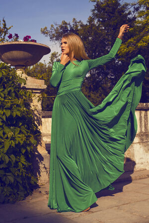 ladylike:   fashion photo of beautiful model with short blond hair wearing luxurious green dress posing at summer park  Stock Photo