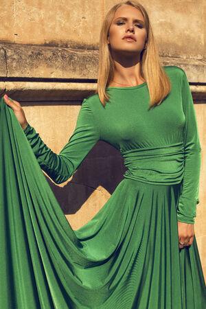 ladylike: fashion photo of beautiful model with short blond hair wearing luxurious green dress
