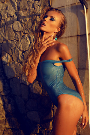 sexy shower: fashion photo of sexy beautiful girl with long blond hair in swimsuit taking shower on sunset beach