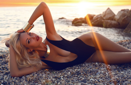 fashion photo of sexy beautiful woman with blond hair in black swimsuit posing on sunset beach