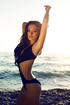 fashion photo of sexy beautiful brunette in black swimsuit posing on sunset beach